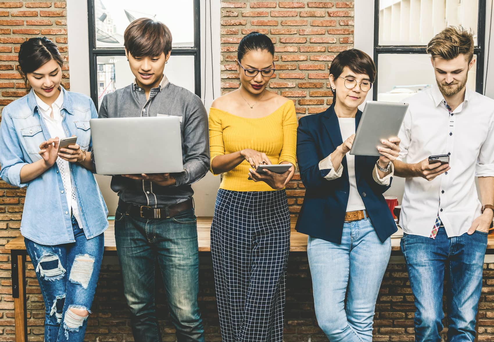 Group Of Asian and Multiethnic Business people with casual suit using the technology mobile, tablet, laptop and computer for working or social network in modern Office,people business group concept