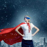 Young confident super businesswoman in mask and cape